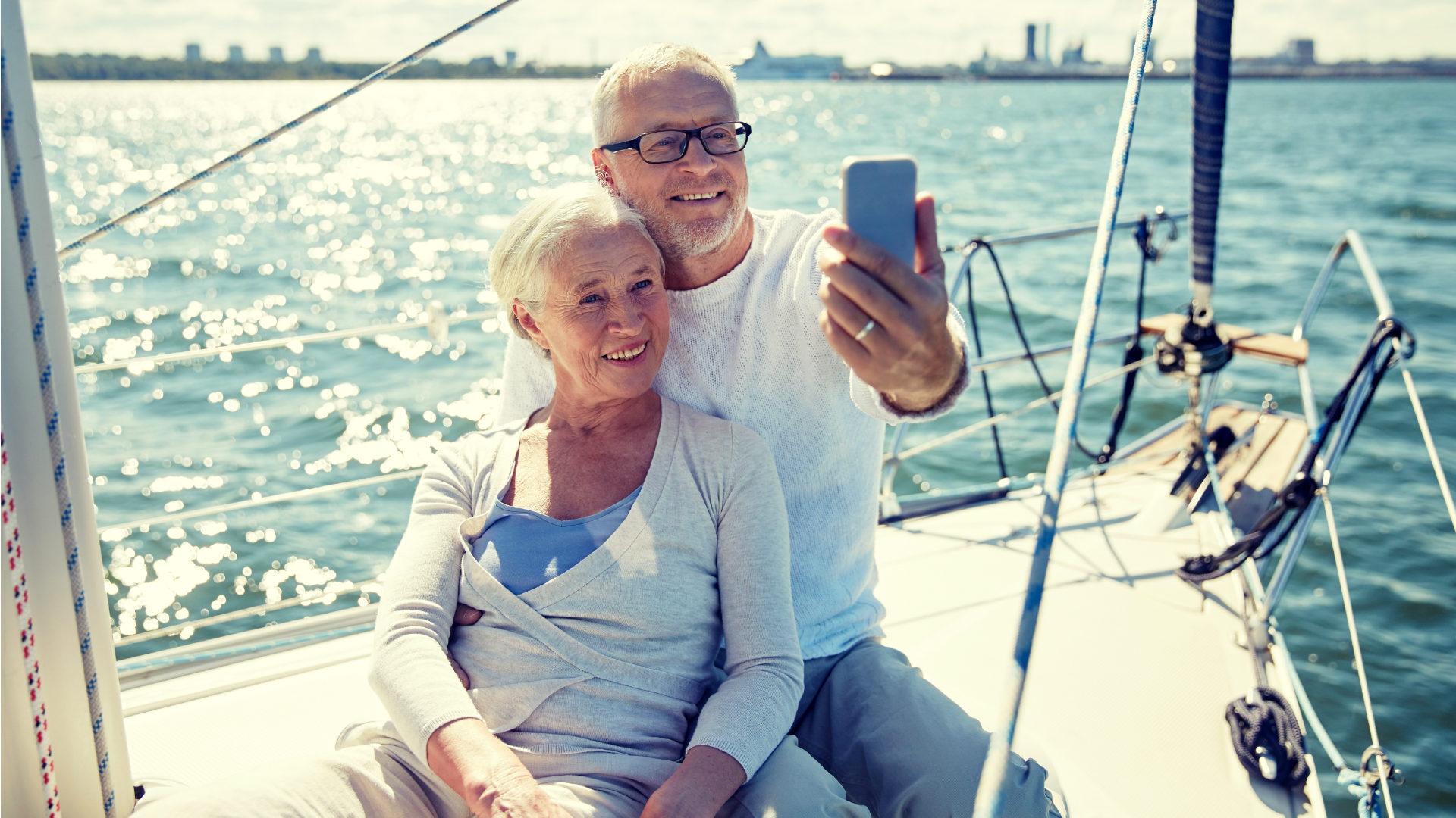 Casal mais velho tira selfie em iate: diferentes tipos de previdência privada ajudam a poupar para a aposentadoria