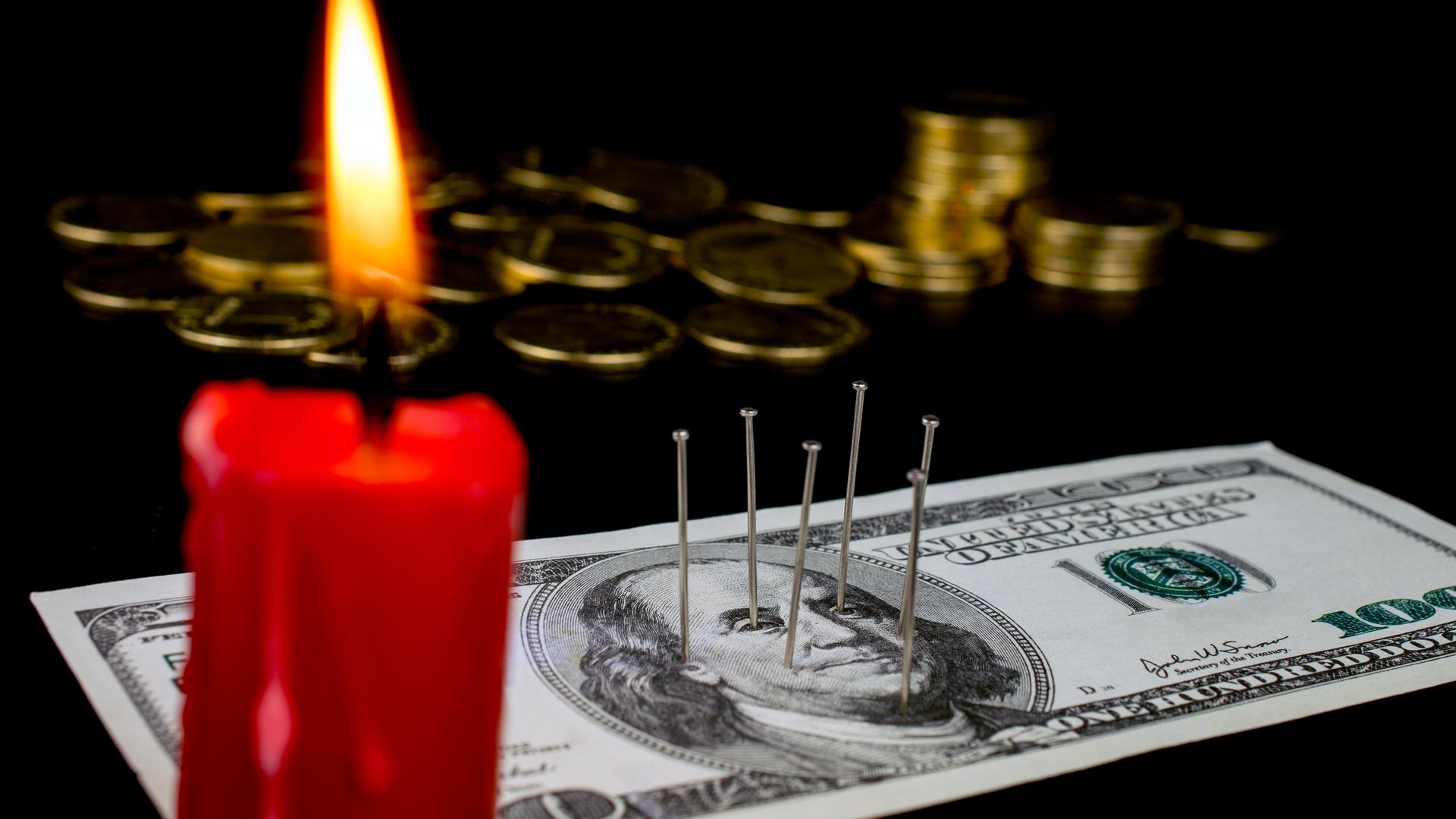 Notas de dólar num ritual macabro, com pregos espetados e velas acesas