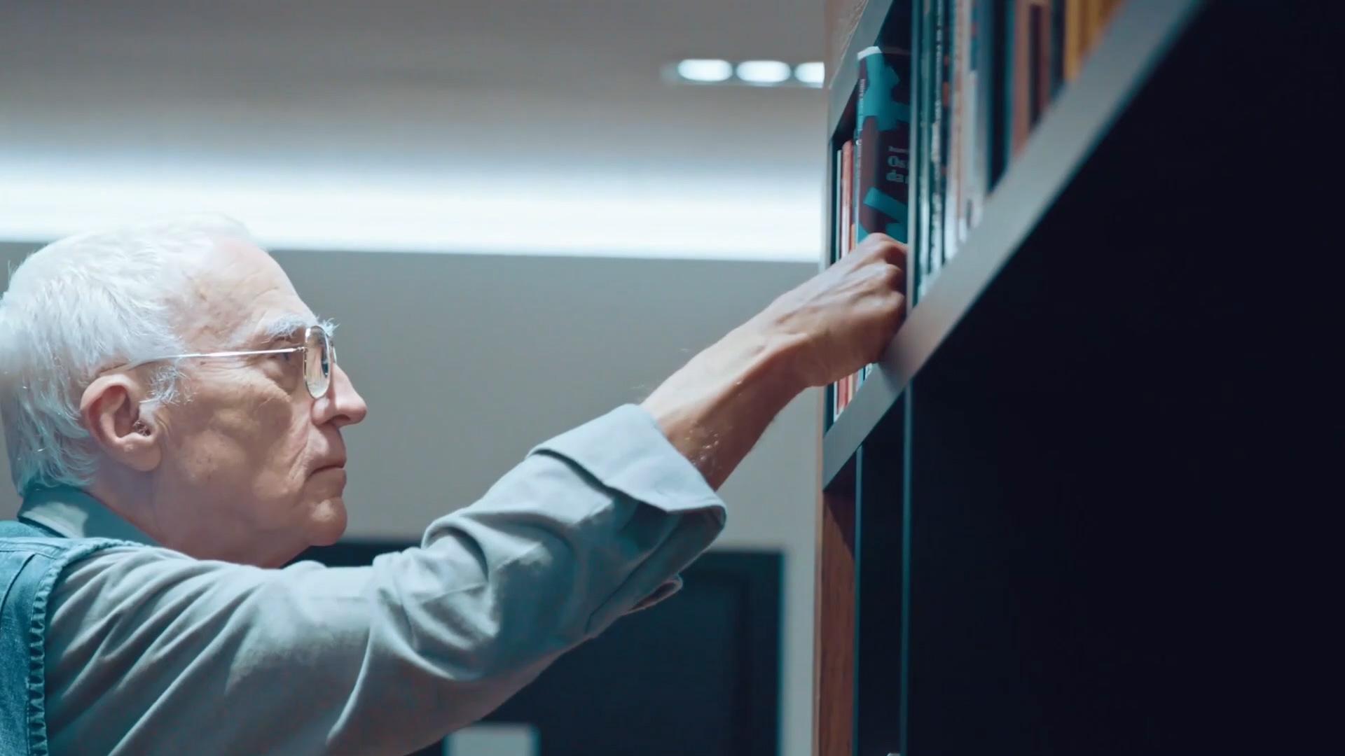 Ivan Sant'Anna pegando um livro na estante