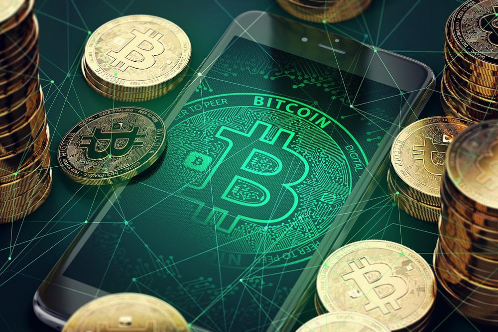 Imagem mostra celular com símbolo do bitcoin