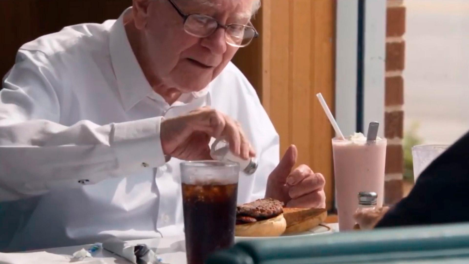 Warren Buffett come hambúrguer durante conversa com Bill Gates