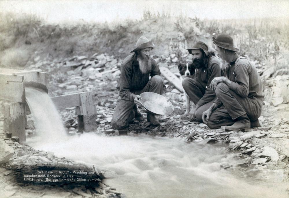 Três homens, com cão, procurando ouro em um riacho nas Colinas Negras de Dakota do Sul em 1889